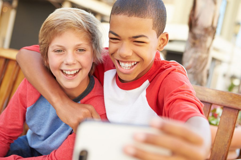 42310084 - two boys sitting on bench in mall taking selfie
